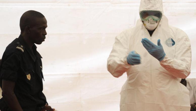A l'aéroport de Dakar, un personnel sanitaire montre comment s'équiper pour se protéger d'Ebola, le 8 avril 2014. AFP PHOTO / SEYLLOU