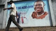 Un partisan du président déchu Laurent Gbagbo passe devant une affiche annonçant une conférence de presse de l'ex-première dame de Côte d'Ivoire Simone Gbagbo, en décembre 2013. AFP PHOTO / HERVE SEVI