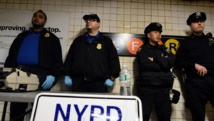 Des officiers de la police new-yorkaise déployés à une station du métro du Queens au lendemain de l'attaque à la hache de Zale Thompson dans ce même quartier, le 24 octobre. AFP PHOTO/Jewel Samad