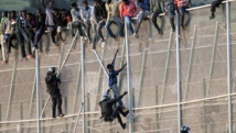 Des officiers de la Garde civile espagnole tentent d'arrêter les migrants africains qui veulent rejoindre l'Espagne par l'enclave de Melilla, en territoire marocain, le 15 octobre 2014. REUTERS/Jesus Blasco de Avellaneda
