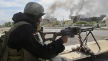 Un membre des forces de sécurité irakiennes tire sur une position islamiste, 115 km au nord de Bagdad, le 24 novembre 2014. REUTERS/Stringer