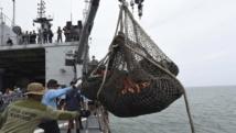 Les équipes techniques chargées de l'enquête sur les causes de l'accident remontent à bord d'un navire de la marine indonésienne des restes du vol QZ8501 d'AirAsia, le 3 janvier REUTERS/Adek Berry/Pool