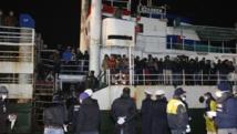 Des migrants attendent de débarquer du cargo Ezadeen au port de Corigliano, le 3 janvier 2015. REUTERS/Antonino Condorelli