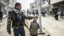 Un combattant des forces de défense kurdes avec un enfant à Kobane, en Syrie, le 28 janvier 2015. AFP PHOTO / BULENT KILIC