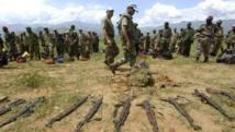 Des soldats de l'ONU inspectent des armes des FDLR dans un camp de désarmement. AFP PHOTO/JOSE CENDON