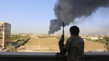Un milicien regarde la colonne de fumée s'élever depuis un dépôt de carburant de l'aéroport de Tripoli, le 2 août 2014. REUTERS/Hani Amara