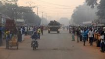 Dans une rue de Bangui, un blindé de Sangaris patrouille au loin. AFP PHOTO / PACOME PABANDJI
