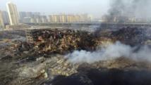 Le site de l'explosion à Tianjin d'où se dégagent encore des fumées, avec les habitations toutes proches en toile de fond, le 15 août 2015. REUTERS/Stringer