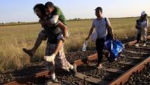 Une famille de migrants syriens à la frontière serbo-hongroise, près de Roszke, le 26 août 2015. REUTERS/Bernadett Szabo