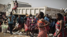 Au Swaziland, les jeunes filles descendent des camions pour se préparer à la danse des roseaux. AFP PHOTO/GIANLUIGI GUERCIA