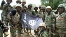 Des soldats nigérians posent devant le drapeau de Boko Haram après avoir démantelé un camp de la secte armée dans l'Etat du Yobe, en février 2015. AFP PHOTO/HO/NIGERIAN ARMY