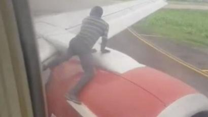 Un homme arrêté sur l'aile d'un avion peu avant le décollage