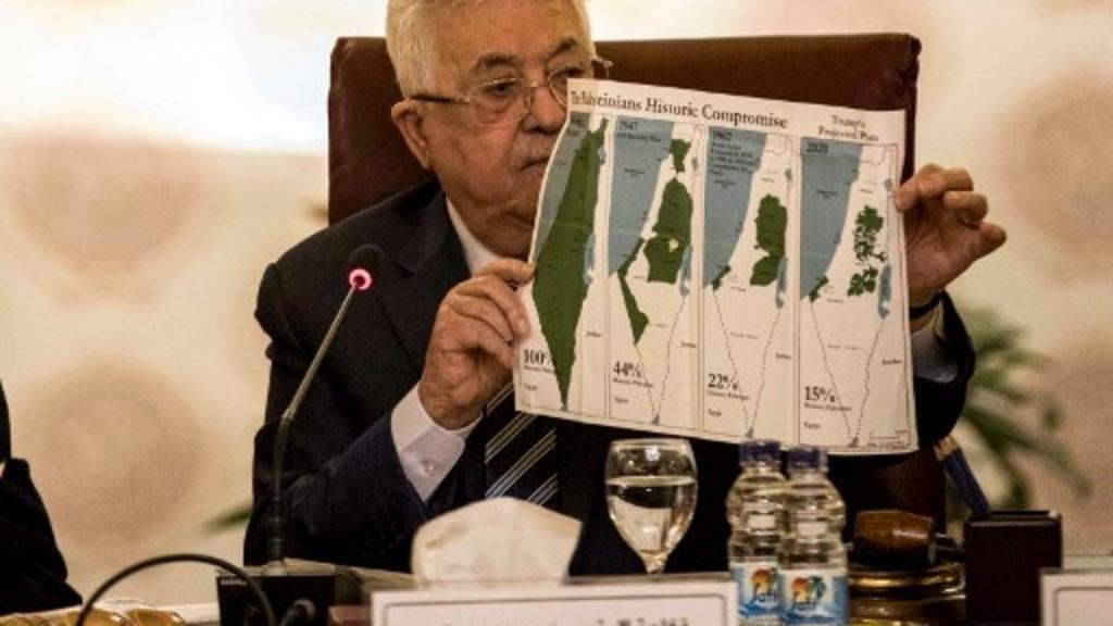 Le président de l'Autorité palestinienne, Mahmoud Abbas, montre des cartes de la Palestine où l'on voit le plan de partition de l'ONU de 1947, les frontières de 1948-67 et une carte sans les zones annexées par Israël, au Caire, le 1er février 2020. Khaled DESOUKI/AFP