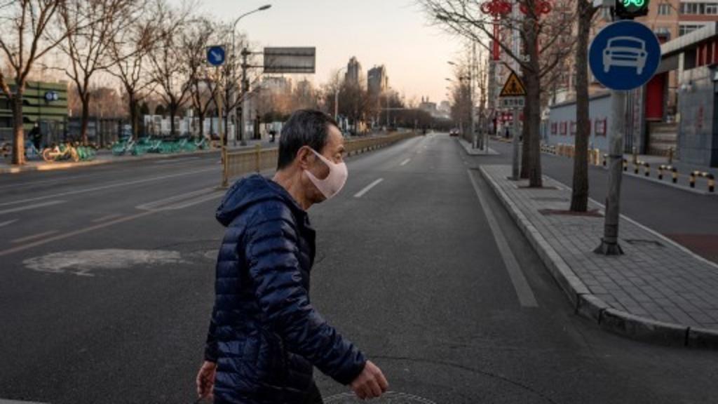 Un homme dans une rue déserte de la ville de Wuhan. Le 31 janvier 2020. NICOLAS ASFOURI / AFP