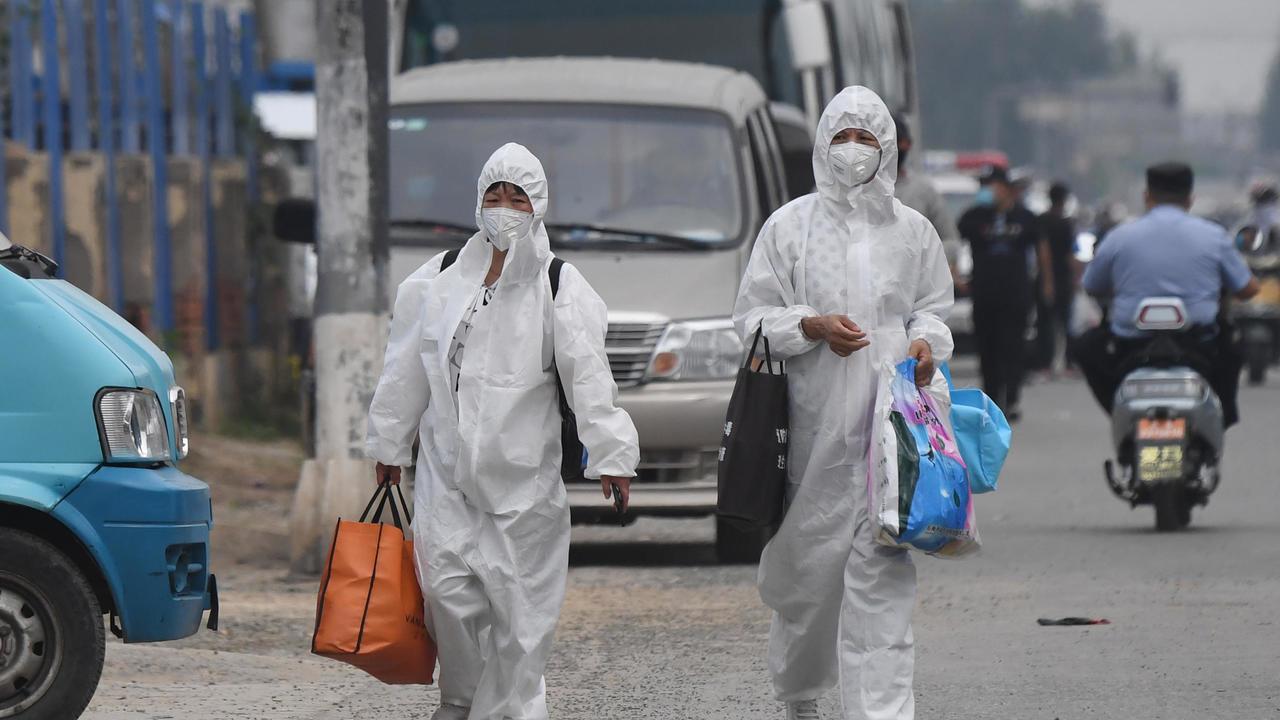 Deux femmes en combinaison de protection près du marché de Xinfadi, d'où un nouveau foyer est apparu à Pékin, le 13 juin 2020. GREG BAKER / AFP