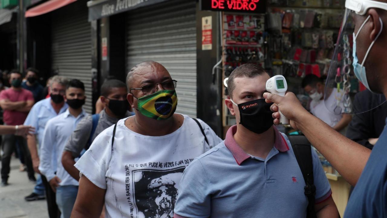 Prise de température avant l'accès aux grandes surfaces, les «malls», qui ont rouvert à Sao Paulo, au Brésil, le 11 juin 2020, malgré les chiffres alarmants de contamination au Covid-19. REUTERS/Amanda Perobelli