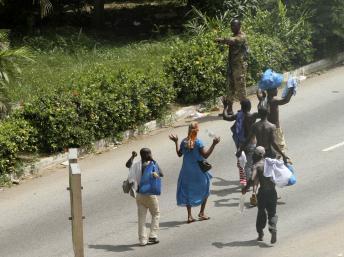 Des civils passent les mains en l'air devant un soldat fidèle à Laurent Gbagbo autour du palais présidentiel, à Abidjan le 3 avril 2011, pendant la crise postélectorale. REUTERS/Luc Gnago