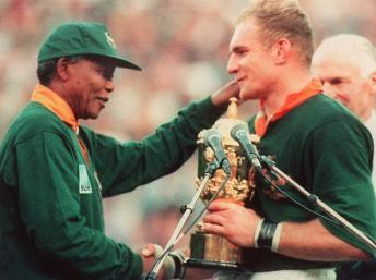 Nelson Mandela remet le trophée William Webb Ellis au capitaine de l'équipe nationale sud-africaine de rugby à XV, François Pienaar, le 24 juin 1995. AFP / JEAN-PIERRE MULLER