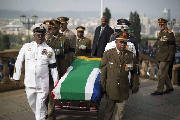 Le dernier hommage de l'ANC à Nelson Mandela : le président Jacob Zuma entre Graça Machel, la veuve de Nelson Mandela et Winnie Mandela, son ex-épouse, ce samedi 14 décembre sur la base aérienne de Waterkloof. REUTERS/Yves Herman