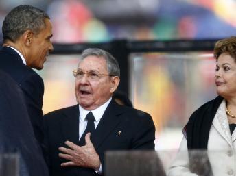 Echange historique entre Barack Obama et Raul Castro, le 10 décembre 2013 lors des obsèques de Nelson Mandela à Soweto, en présence de Dilma Rousseff. REUTERS/Kai Pfaffenbach/Files