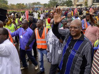 Roch Marc Christian Kabore (d.), ancien président de l'Assemblée nationale burkinabè, salue la foule à son arrivée dans le cortège de l'opposition, le 18 janvier 2014 à Ouagadougou. AFP PHOTO/AHMED OUOBA