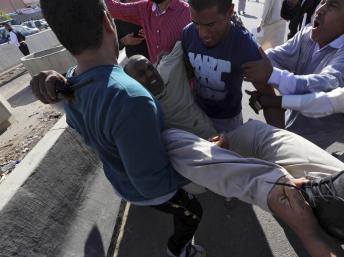 Un blessé transporté après les tirs d'une milice contre la foule venue demander son départ, le 15 novembre 2013 à Tripoli, en Libye. REUTERS/Stringer