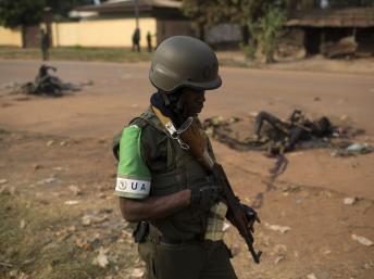 Un soldat de la Misca lors d'une patrouille à Bangui, passe devant les corps calcinés de deux musulmans tués par une foule hostile, dimanche 26 janvier à Bangui. REUTERS/Siegfried Modola