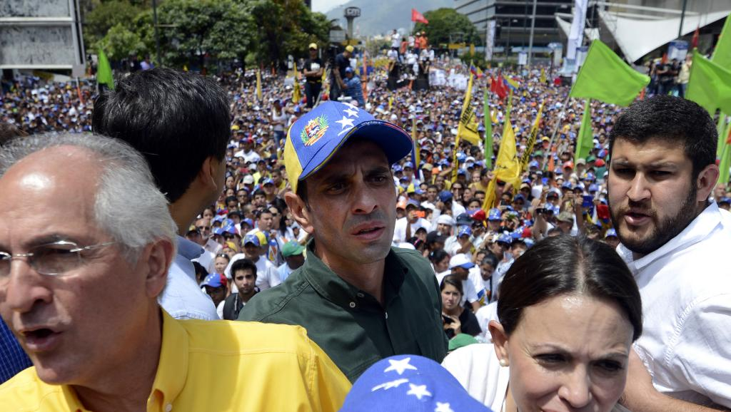 Henrique Capriles, en vert avec une casquette, le 22 février 2014 à Caracas. AFP PHOTO / JUAN BARRETO