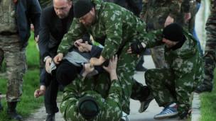 Des soldats russes arrêtant de force un soldat ukrainien sans prévenir.