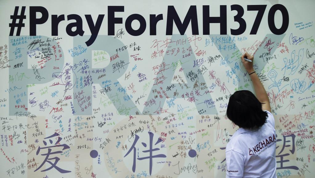 Ne pas oublier les passagers et membres d'équipage du vol MH370 de la Malaysia Airlines : les habitants de Kuala Lumpur laissent des messages sur ce mur du souvenir improvisé au siège de l'Association sino-malaisie.