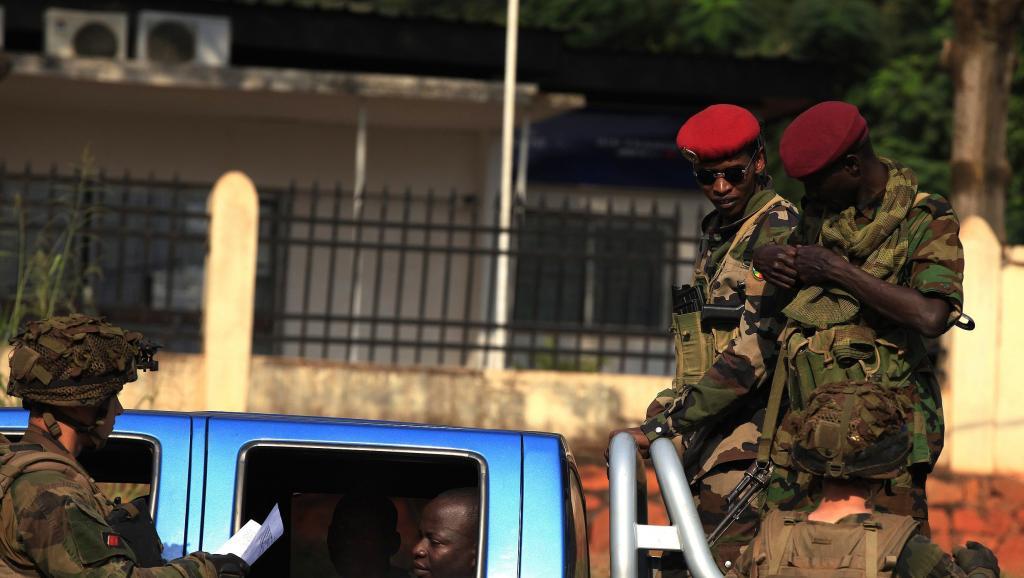 Des militaires français fouillent un véhicule alors que des soldats Seleka surveillent, à Bangui, le 23 décembre 2013.