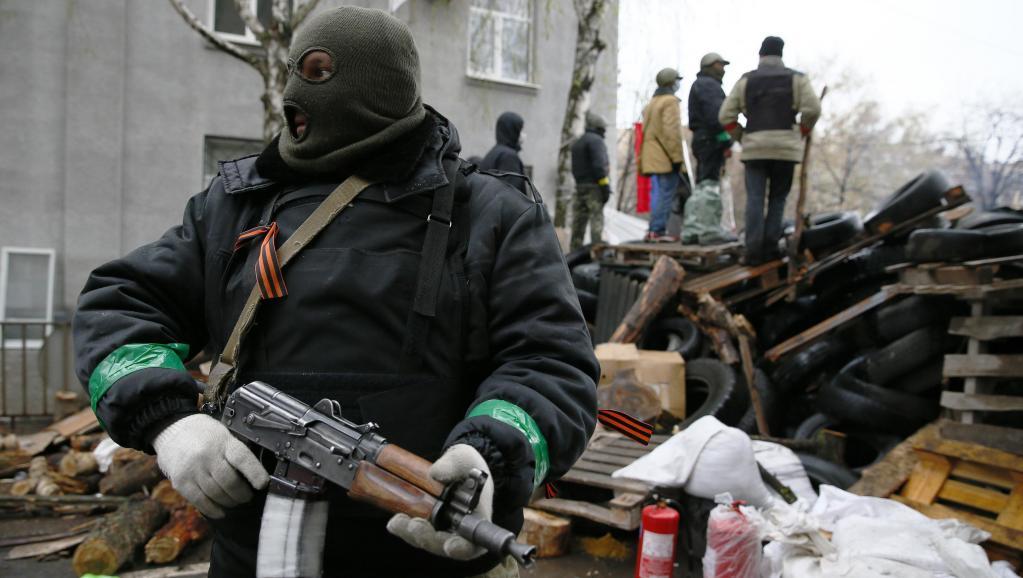 Un homme armé devant le siège de la police à Slaviansk, le 13 avril 2014.