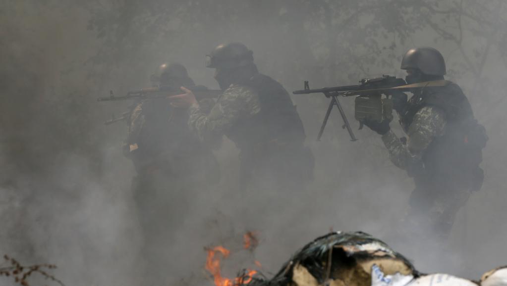 Des éléments des forces de sécurité ukrainiennes passent un barrage abandonné par les séparatistes pro-Russes à Slaviansk, le 24 avril.