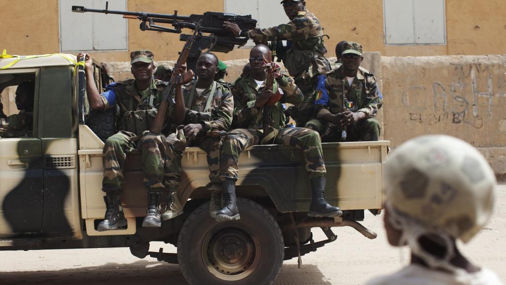 Une patrouille de militaires maliens passe devant des civils. REUTERS/Joe Penney