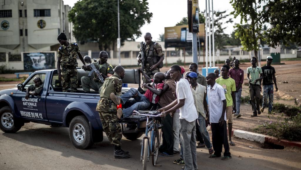 Des membres de la gendarmerie nationale évacuent un blessé vers l'hôpital de Bangui, le 29 mai 2014. AFP PHOTO/MARCO LONGARI