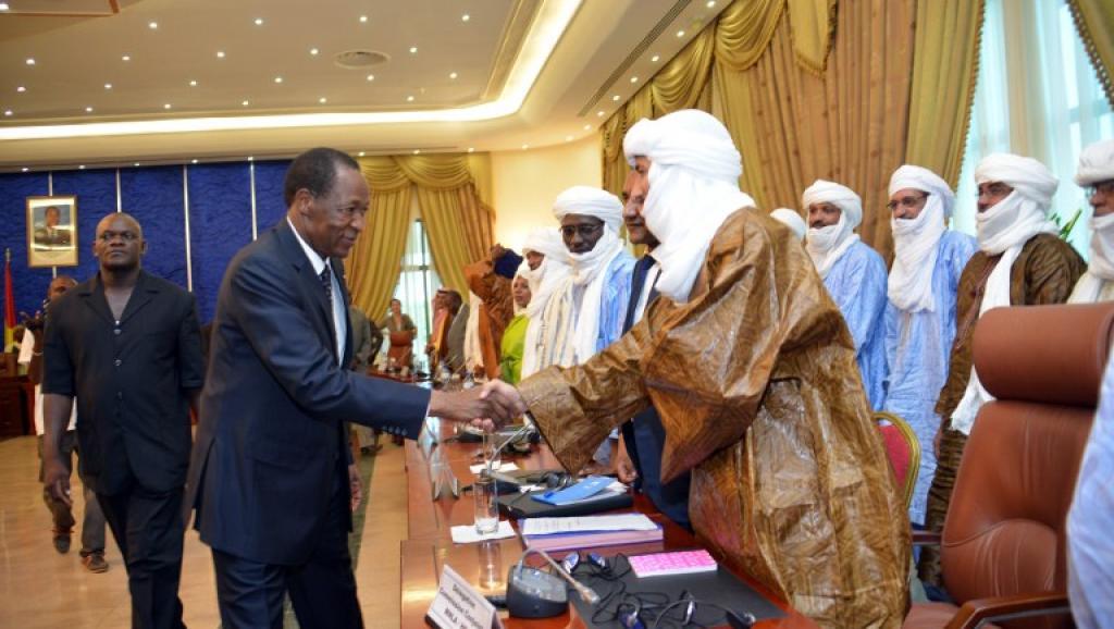 Le président burkinabè, Blaise Compaore (c) salue Bilal Ag Acherif, le secrétaire général du Mouvement national de libération de l'Azawad (MNLA), après la signature de l'accord, le 18 juin 2013 à Ouagadougou. AFP/AHMED OUOBA