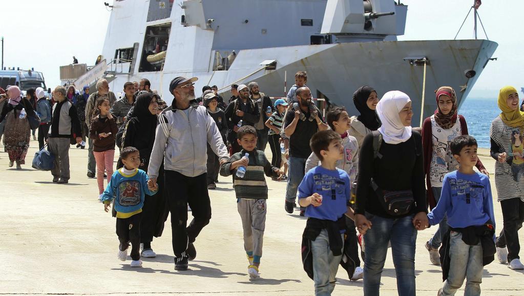 Des migrants débarquent dans le port d'Augusta en Sicile après avoir été secourus par un navire militaire, le 22 mai 2014.