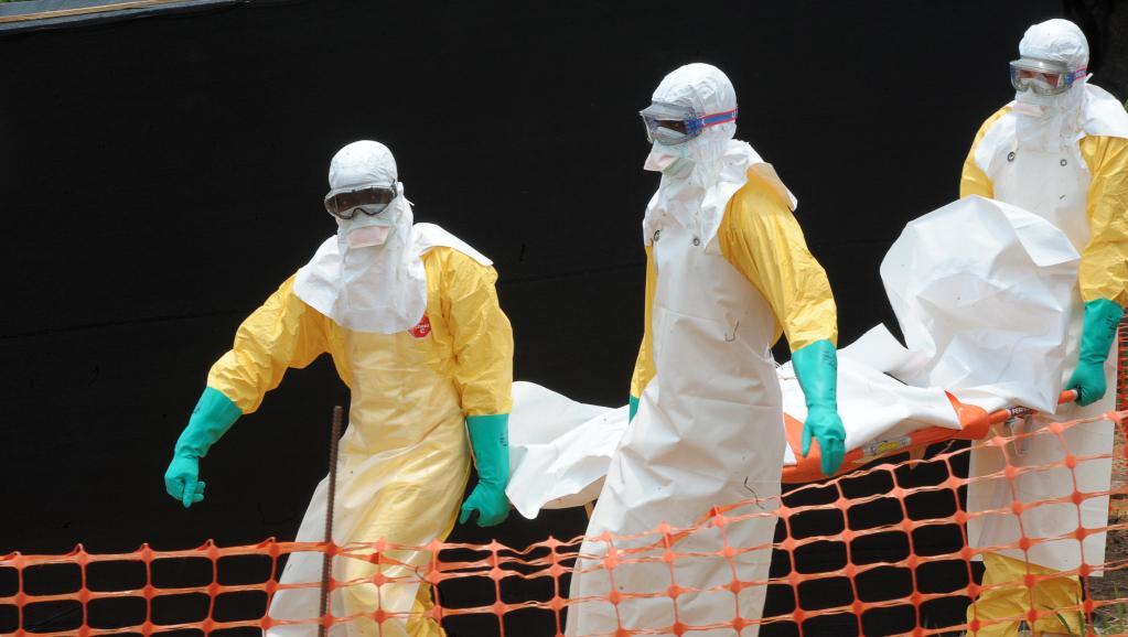 personnel de Médecins sans frontières porte le corps d'une personne décédée du virus Ebola, le 1er avril 2014, à Guekedou, en Guinée, dans un centre pour victimes de la fièvre hémorragique. AFP PHOTO / SEYLLOU