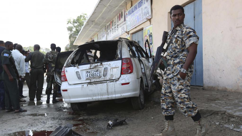 Un soldat somalien est posté à côté de la carcasse de la voiture du journaliste Yusuf Keynan, dans laquelle ce dernier se trouvait quand elle a explosé, le 21 juin 2014, à Mogadiscio. REUTERS/Feisal Omar