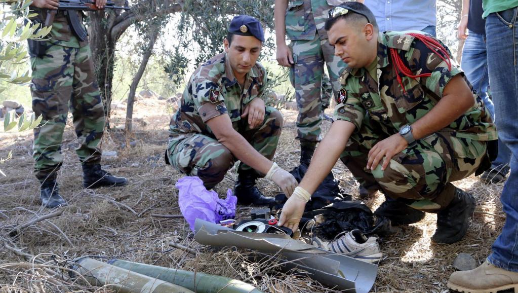 Des soldats libanais inspectent les débris d'un obus qui aurait été tiré du Liban vers Israël, au Sud-Liban, le 11 juillet 2014. REUTERS/Karamallah Daher