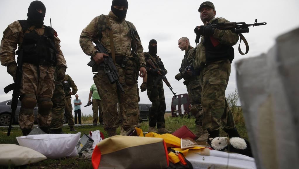 Des miliciens séparatistes à proximité de débris de l'avion abattu au-dessus de l'est de l'Ukraine, jeudi 17 juillet. REUTERS/Maxim Zmeyev