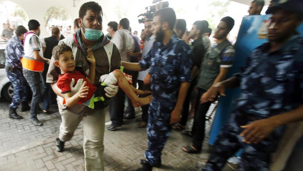 Un Palestinien transporte un enfant blessé dans le bombardement du quartier de Chajaya, à l'hôpital de Gaza-Ville, ce dimanche 20 juillet. REUTERS/Suhaib Salem