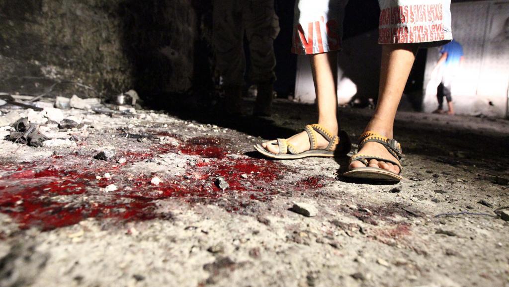 Un jeune homme se tient sur les lieux d'un double attentat suicide qui a tué 4 soldats sur une base militaire à Benghazi, le 22 juillet. AFP PHOTO/Abdullah DOMA