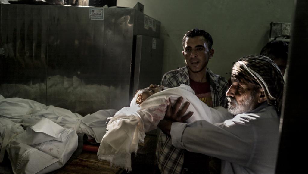 Au total, 132 enfants auraient été tués depuis le début de l'offensive israélienne dans la bande de Gaze. Ici le corps d'un enfant est remis à un parent, à Beit Lahia, le 23 juillet 2014.