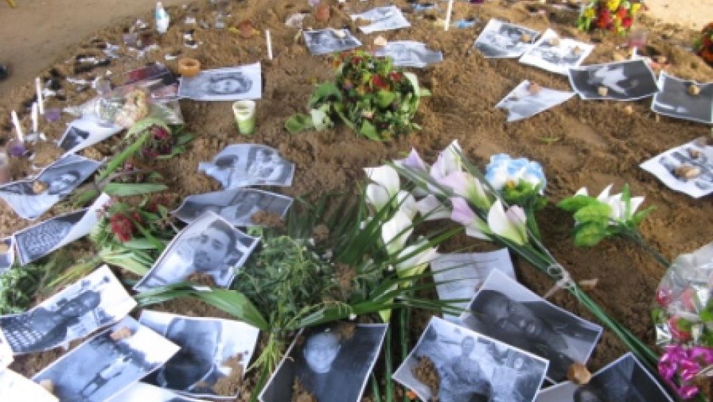 A côté de la liste des passagers du vol AH 5017 d'Air Algérie, des proches et anonymes ont déposé des fleurs, bougies et des photos de certaines victimes de la catastrophe. RFI/Yaya Boudani