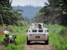 Des membres de la population locale saluant le passage d'un véhicule blindé de transport de troupes de la Monusco qui se dirige vers la ligne de front, dans la région de Beni, province du Nord-Kivu en RDC, le 13 mars 2014.