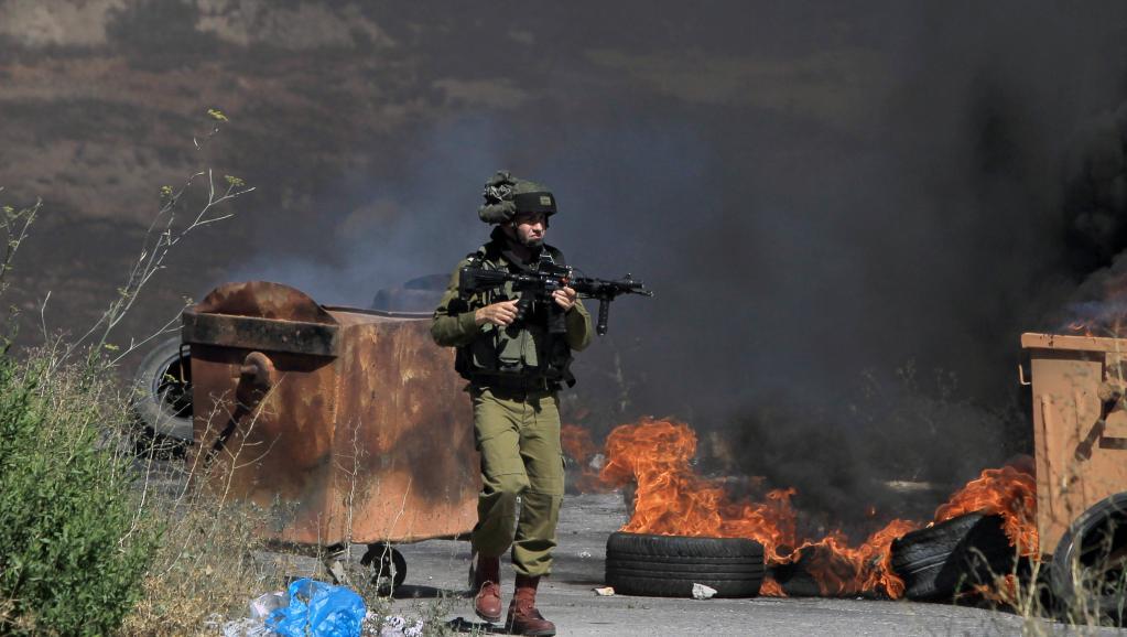 Un soldat israélien aux prises avec des manifestants palestiniens devant les portes de la colonie de Beit El en Cisjordanie, le 25 juillet 2014. AFP PHOTO / ABBAS MOMANI