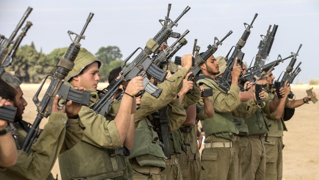 Des soldats israéliens vérifient leurs armes à la frontière sud entre Israël et la bande de Gaza, vendredi 1er août, après l'échec du cessez-le-feu