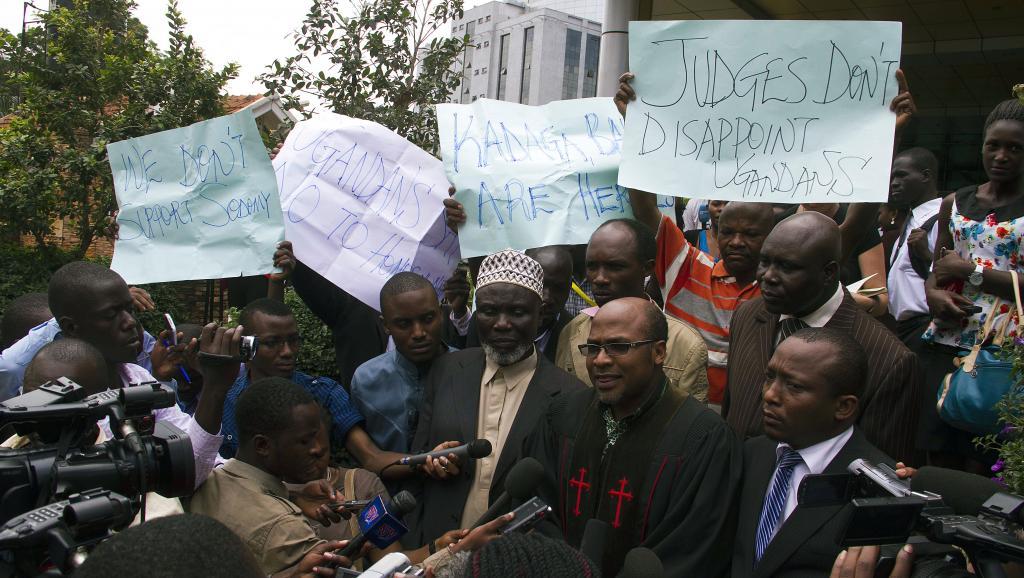 Le pasteur Martin Ssempa (C), entouré de militants anti-gays, s'exprime devant la presse, après que la Cour constitutionnelle a annulé des lois anti-gays, le 1er août 2014.