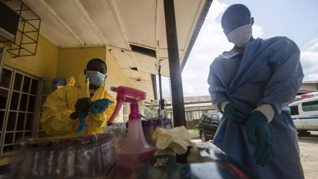 Du personnel médical se protège avant de prélever un patient suspecté d'être porteur du virus Ebola, à Kenema, en Sierra Leone.